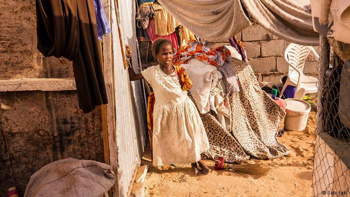 A young girl wearing a dress stands alone in a makeshift house