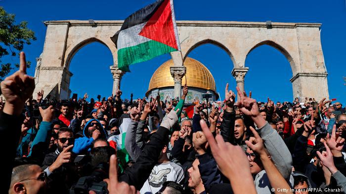 Palestinian protesters shout slogans in front of the Dome of the Rock mosque at the al-Aqsa mosque compound in Jerusalem's Old City. Hundreds of additional police were deployed to control the masses of protestors after Palestinian calls for protests following Friday prayers (photo: Getty Images/AFP/A. Gharabli)