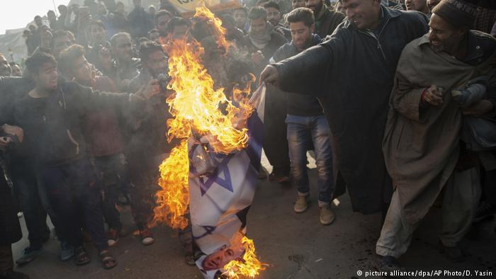 Muslim men burn Israeli and U.S. flags during a protest in Budgam, southwesst of Srinagar, in Indian-controlled Kashmir. Protesters marched in several places in Srinagar and other parts of the region after Friday prayers chanting slogans such as Down with America and Down with Israel (photo: picture-alliance/dpa/AP Photo/D. Yasin)