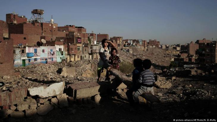 children play on a make shift see-saw made out of a tree trunk in slum area Ezbet Khairallah, Cairo; October 2018 (photo: AP Photo/Nariman El-Mofty)