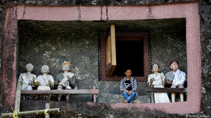 The twenty-one year-old mining engineer in front of the tomb of his deceased great-grandmother in Toraja (photo: Darren Whiteside/Reuters)