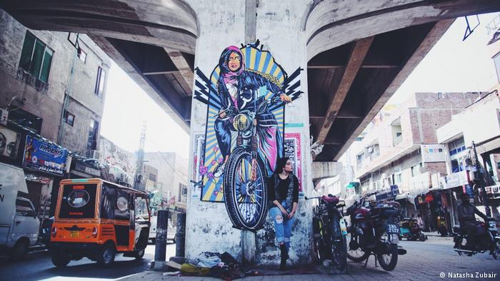 Fashion model Eman Suleman poses in front of graffiti by Shehzil Malik under a bridge in Lahore, Pakistan (photo: Natasha Zubair)
