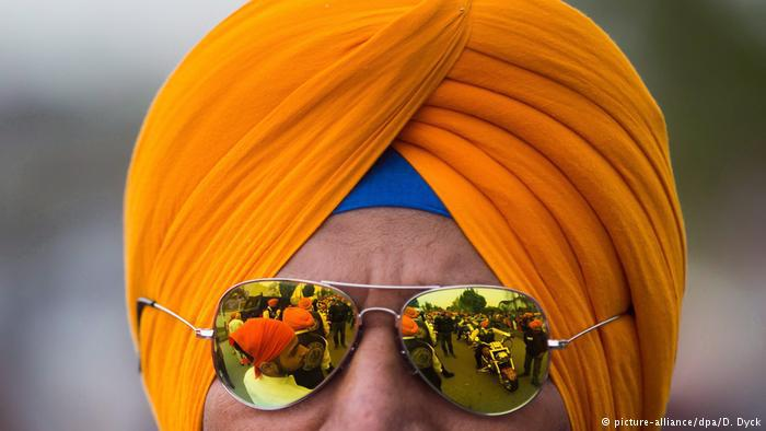 Man wearing an orange Sikh turban (photo: picture-alliance/dpa/D. Dyck)
