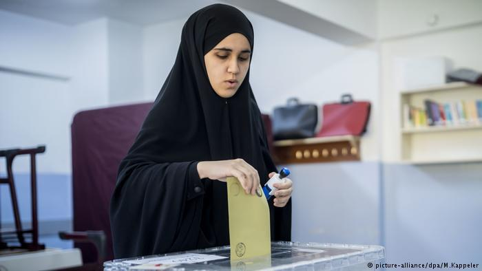 Woman wearing a chador at the ballot box (photo: picture-alliance/dpa/M. Kappeler)