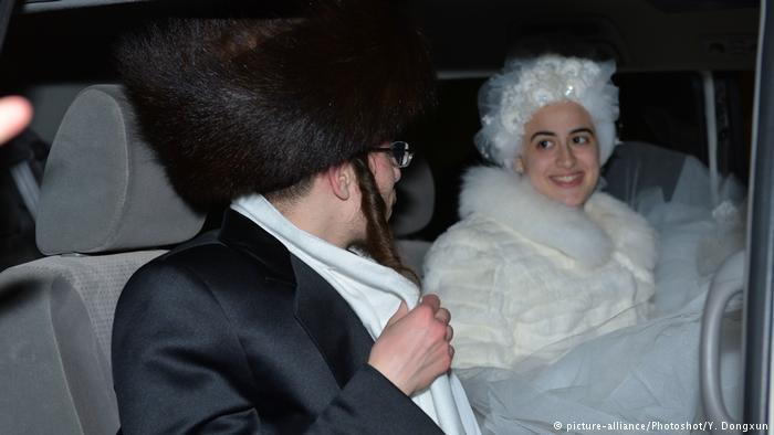 Hasidic man with fur hat and woman wearing a curly white wig in a car (photo: picture-alliance/Photoshot/Y. Dongxun)