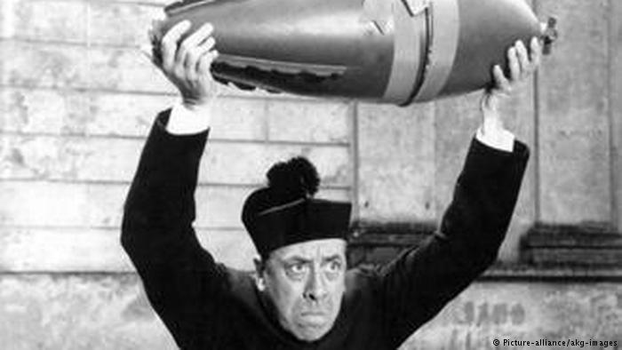 Film still: Don Camillo holds a bomb high over his head (photo: picture-alliance/akg-images)