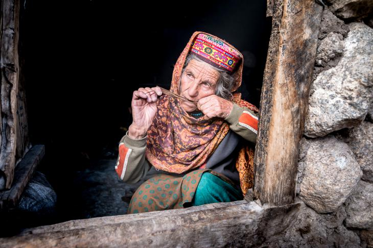 Old Wakhi woman playing a wooden mouth harp in her shepherd's hut (photo: Camille Del Bos)