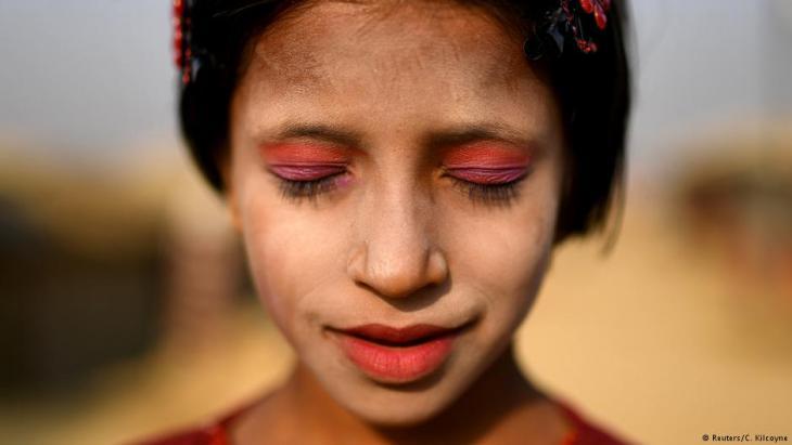 A Rohingya refugee girl named Amina poses for a photograph as she wears thanaka paste at Kutupalong camp in Cox's Bazaar, Bangladesh, 30 March 2018 (photo: Reuters/Clodagh Kilcoyne)