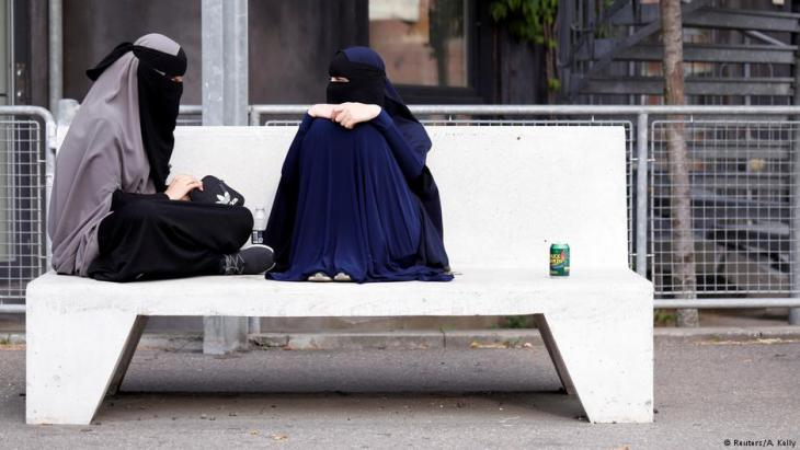 Sabina (left), 21, and Alaa, both students and wearers of the niqab, sit in a park in Copenhagen, Denmark, July 17, 2018 (photo: Reuters/Andrew Kelly)