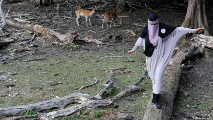 Meryem, 20, a wearer of the niqab and a member of the group Kvinder I Dialog (Women In Dialogue), walks across a log at Dyrehaven, a deer petting park, in Aarhus, Denmark, 27 July 2018 (photo: Reuters/Andrew Kelly)