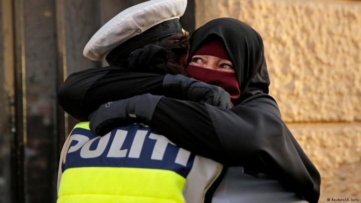 Ayah weeps as she is embraced by a police officer during the demonstration (photo: Reuters/Andrew Kelly)