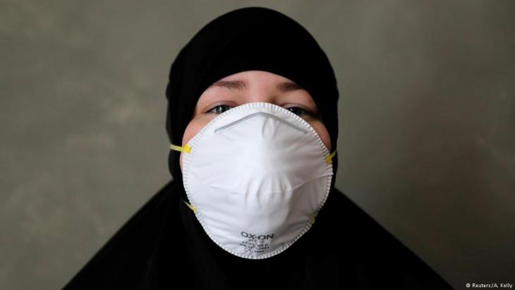 Aicha, 29, from Jutland poses with the mask she wore to the protest (photo: Reuters/Andrew Kelly)