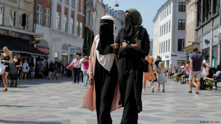 Anna-Bella (L), 26, a home care worker and Amina, 24, a student, both members of the group Kvinder I Dialog (Women In Dialogue) and wearers of the niqab, walk along Stroget, the main shopping strip in Copenhagen, Denmark, 26 July 2018 (photo: Reuters/Andrew Kelly)