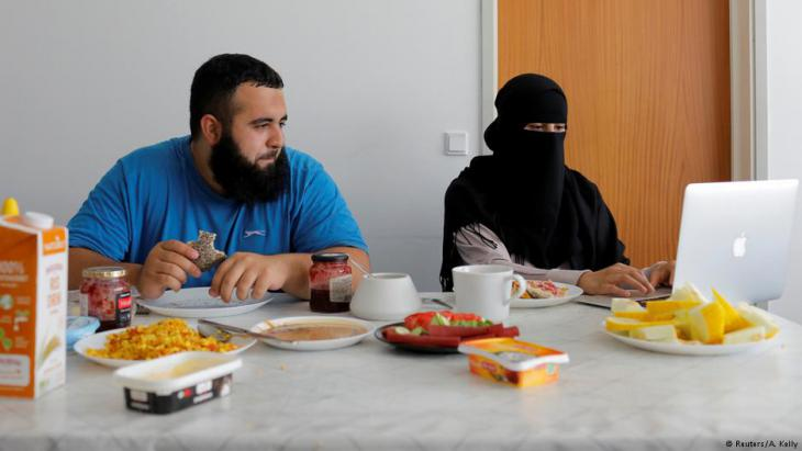 Meryem, 20, a wearer of the niqab and a member of the group Kvinder I Dialog (Women In Dialogue), sits with her husband Ali, 23, as she updates her blog Niqabi Nuancer over a vegan breakfast in Aarhus, Denmark, July 28, 2018 (photo: Reuters/Andrew Kelly)