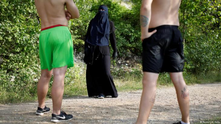 Ayah, 37, a wearer of the niqab, speaks with swimmers during a visit to Karlstrup Kalkgrav, a lake near Karlstrup located outside Copenhagen, Denmark, 18 July 2018 (photo: Reuters/Andrew Kelly)