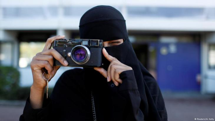 Amina, 24, a wearer of the niqab and a member of the group Kvinder I Dialog (Women In Dialogue), using a camera in Copenhagen, Denmark (photo: Reuters/Andrew Kelly)