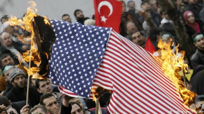 Demonstrators burn a U.S. flag
