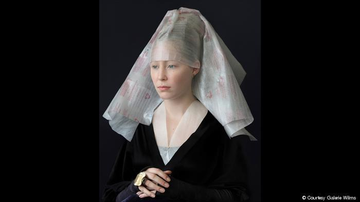 A photograph shows a woman dressed in a Flemish style but with clothing made of recycled materials (photo: Galerie Wilms)