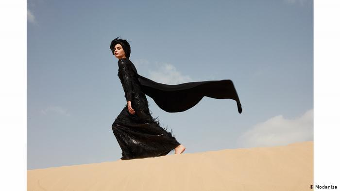 A woman in a black dress with a billowing scarf walks across a sand dune (photo: Modanisa)