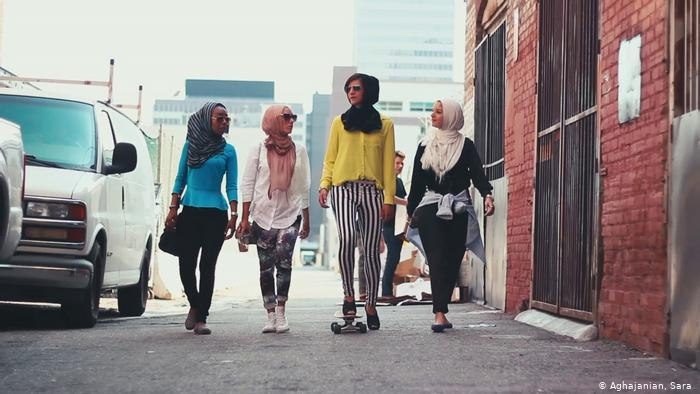 Four young women with headscarves walk along a street (photo: Sara Aghajanian)