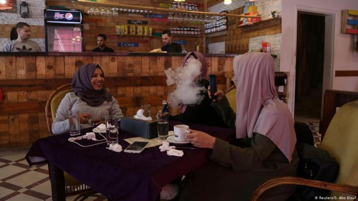 Student Saly Abu Amra (left), 23, a Sharia (Islamic law) and jurisprudence major, looks on as her friend smokes a water pipe at a cafe in Gaza City, 4 December 2018 (photo: Reuters/Samar Abo Elouf)