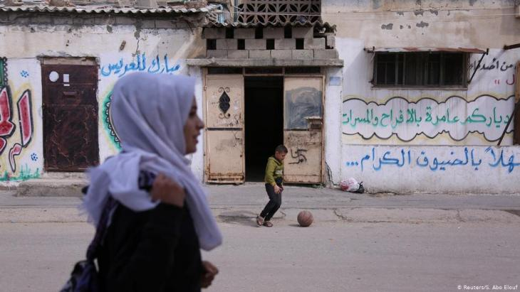 A boy plays ball as Wessal Abu Amra walks home from school in Gaza City (photo: Reuters/Samar Abo Elouf)