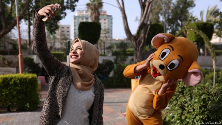 Wessal take a selfie with a person wearing a costume in a public park in Gaza City (photo: Reuters/Samar Abo Elouf)