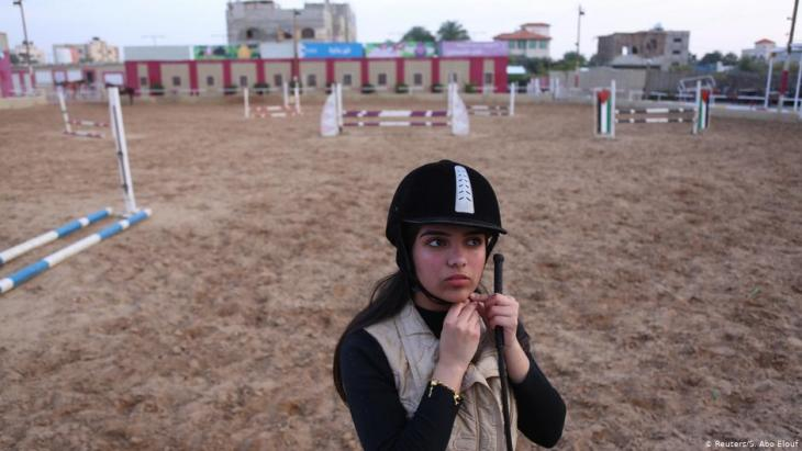 High school student Fatma Youssef adjusts her helmet as she prepares to ride a horse at an equestrian club in Gaza City (photo: Reuters/Samar Abo Elouf)