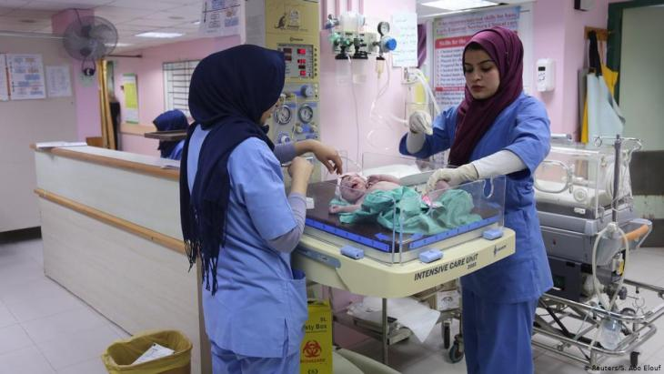Midwife Sara Abu Taqea (right) weighs a new-born in the maternity ward at Gaza's Al-Ahli hospital (photo: Reuters/Samar Abo Elouf)