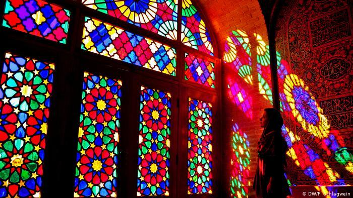 A tourist stands in the coloured lights from the stained glass windows in the Mosque of Nasir-ol-Molk (photo: DW/F. Schlagwein)
