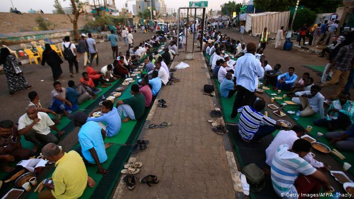 Protesters sit in rows on the ground while breaking fast (photo: Getty Images/AFP/A. Shazly)