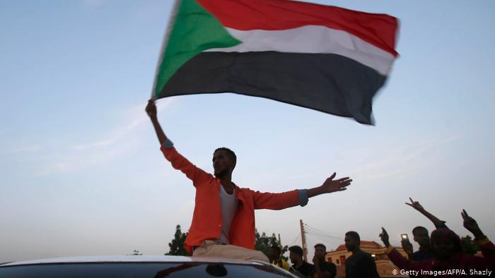 A man waves the Sudanese flag from atop a car (photo: Getty Images/AFP/A. Shazly)