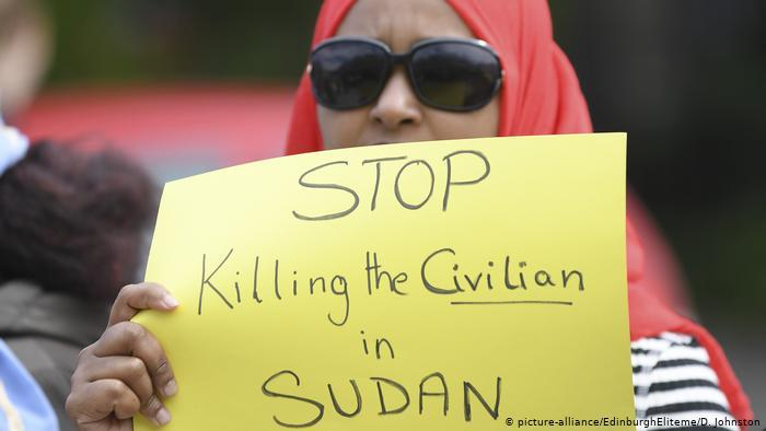 "A Sudanese protester in Edinburgh holds up a poster reading ""Stop killing civilians in Sudan"" (photo: picture-alliance/EdinburghEliteme/D. Johnston)"