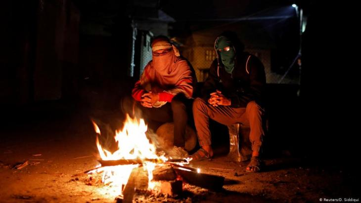 Kashmiri men on night-time guard duty warm themselves at a barricade (photo: Reuters/D. Siddiqui)