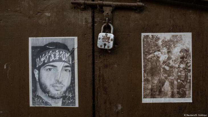 Pictures of dead militants are seen pasted on the door of a closed shop (photo: Reuters/D. Siddiqui)