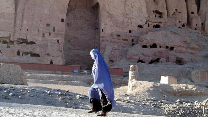 A woman walks past an enormous Buddha niche carved into the rock face in Bamiyan province, Afghanistan, 2007. The ancient Buddha statues were destroyed by the Taliban in March 2000, despite a national and international outcry to halt the destruction (photo: AP Photo/Amir Shah)