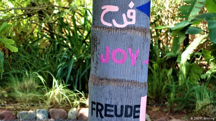 """Morocco ANIMA Garden - close-up of a tree trunk with the word """"Joy"""" painted in different languages (photo: DW/V. Witting)"""