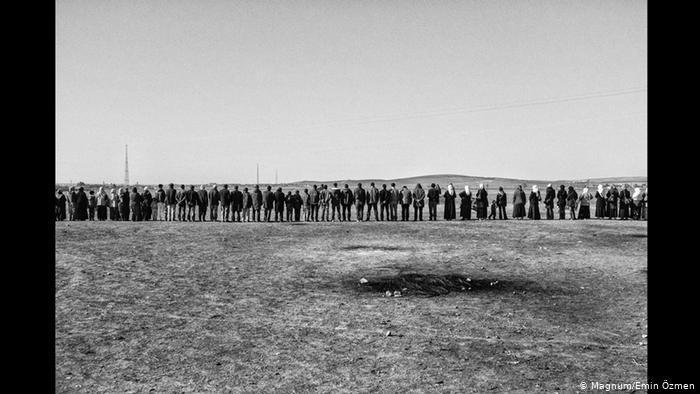 A chain of Kurds stands in a barren landscape (photo: Magnum/Emin Ozmen)