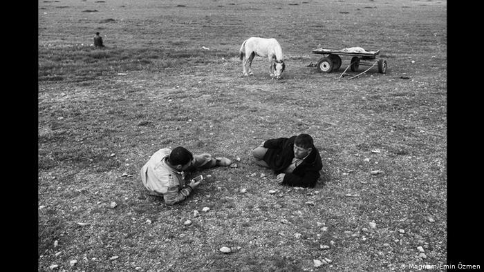 A balck-and-white picture shows two men lying on the ground, with one checking his phone while horse and cart stand in the background (photo: Magnum/Emin Ozmen)