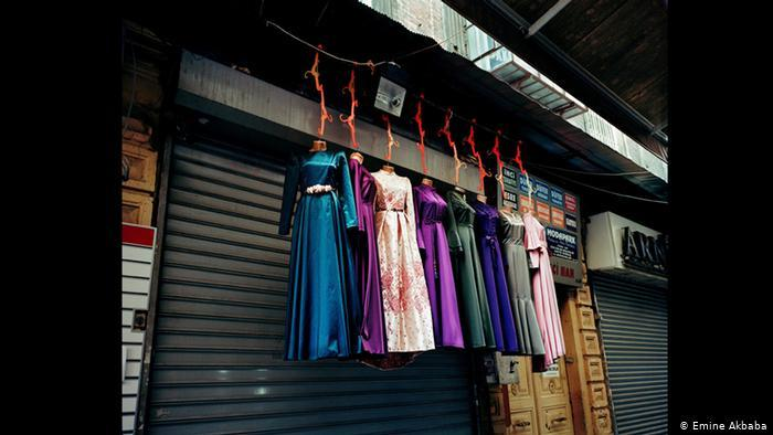 Colourful dresses suspended in front of a closed shop front (photo; Emine Akbaba)