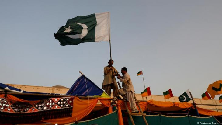Men install Pakistan's national flag on a stall ahead of the Hazara Culture Day celebration at the Qayum Papa Stadium in Mariabad, Quetta (photo: Reuters/A. Soomro)