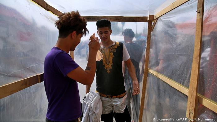 Inside a makeshift wooden frame lined with plastic, a young man sprays down another with a small spray bottle