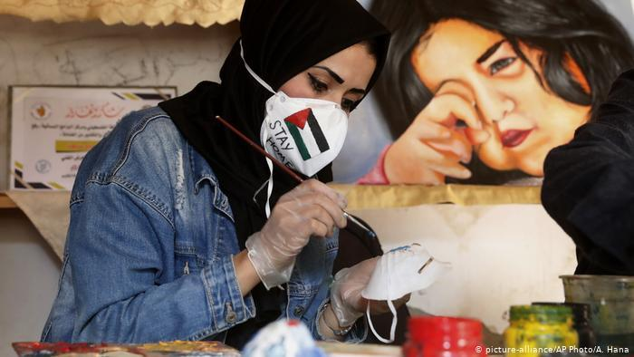 Palestinian artist Samah Saed decorates a protective face mask (photo: picture-alliance/AP Photo/A. Hana)