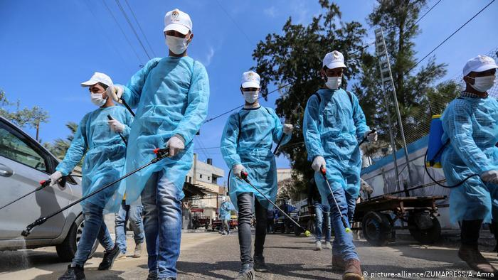 Palestinian workers spray disinfectant as a preventive measure amid fears of the spread of the coronavirus disease (photo: picture-alliance/ZUMAPRESS/A. Amra)