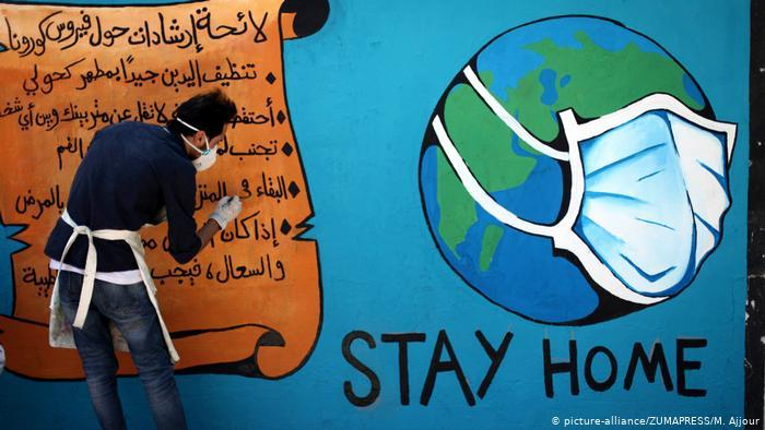 "A Palestinian artist draws a ""stay home"" mural as part of an awareness-raising campaign about the spread of coronavirus (photo: picture-alliance/ZUMAPRESS/M. Ajjour)"