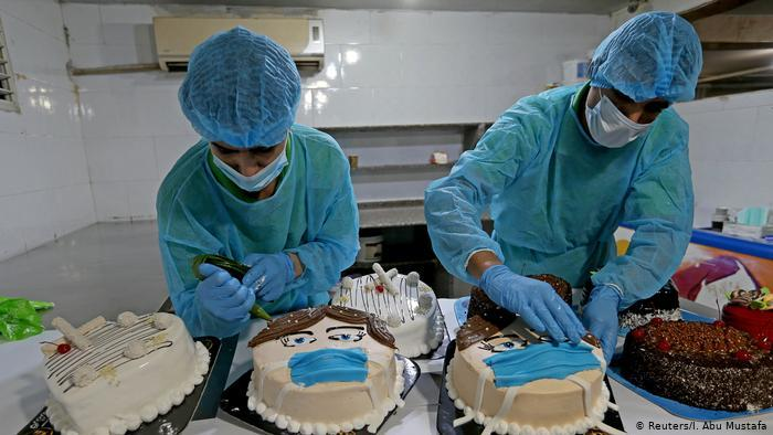 Palestinian bakers decorate cakes shaped like faces wearing protective masks (photo: Reuters/I. Abu Mustafa)