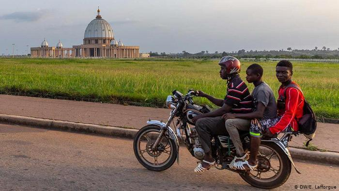 Three young men on a motorbike ride past the Basilica of Our Lady of Peace (photo: DW/E. Lafforgue)