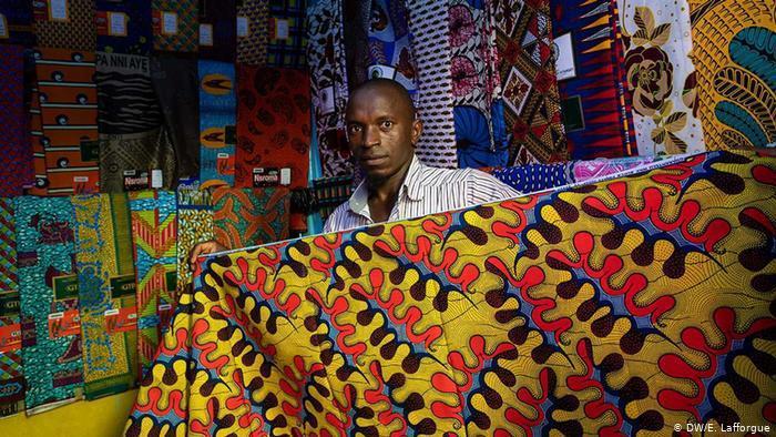 A man holds a traditional Ivorian wax print fabric (photo: DW/E. Lafforgue)