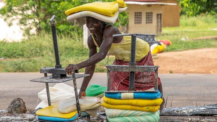 An Ivorian woman from the Femmes Battantes Cooperative wraps attieke - traditional couscous - in bags (photo: DW/E. Lafforgue)