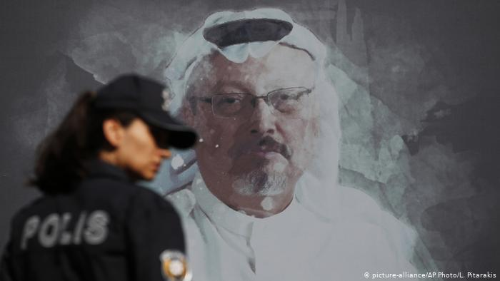 Police officer stands in front of a photo of murdered journalist Jamal Khashoggi in Istanbul, Turkey (photo: picture-alliance/AP Photo/L. Pitarakis)